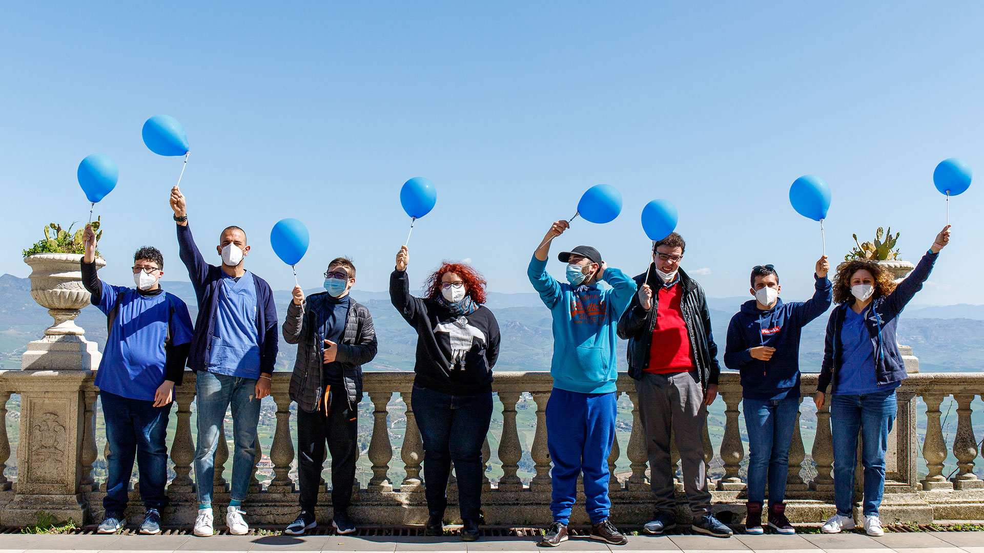 persone con palloncini blu davanti a balconata
