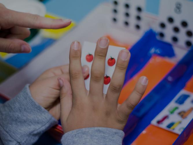 Mani di bambino con carta in mano e mano operatrice