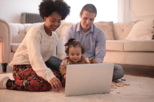 mamma papà e figlia seduti sul tappeto guardano un computer sorridendo