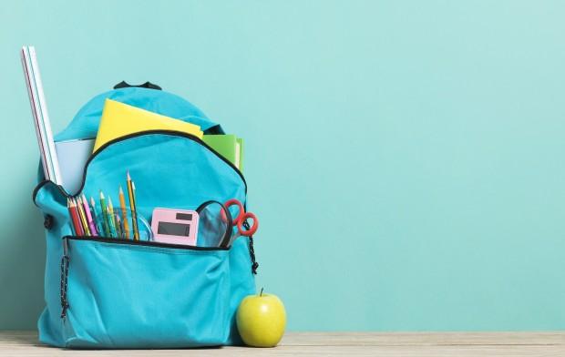 Zaino scolastico pieno di oggetti che escono dalle tasche e una mele appoggiata al suo fianco